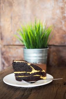 Торт шоколадный на белой тарелке на деревянном столе с декоративным растением