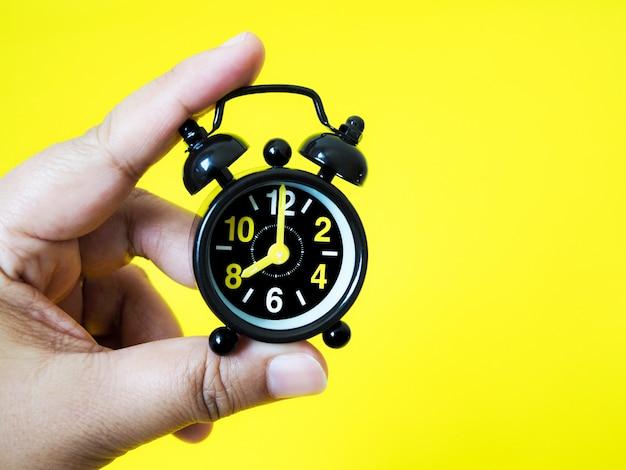 黄色の背景にヴィンテージの黒い目覚まし時計を持っている手