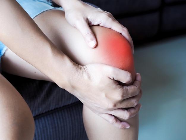 アジアの女性は足をマッサージし、膝の痛み、関節炎または靭帯の損傷から痛みを和らげます。