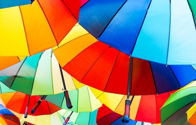 虹色の赤、青、緑、黄色、オレンジ色のカラフルな傘のクローズアップ