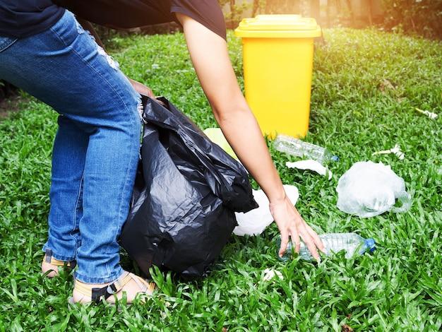 アジアの女性は庭に置かれた黄色いゴミの入った黒い袋にゴミを集めます。