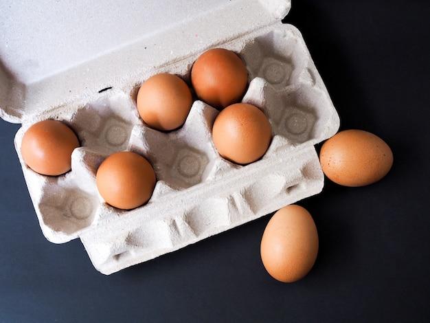 茶色の段ボールからのパネルで新鮮な鶏の卵
