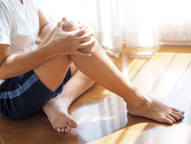 アジアの女性は、膝の痛み、筋肉または腱の炎症を伴う足のマッサージに手を使用します。痛風による脚の痛み。