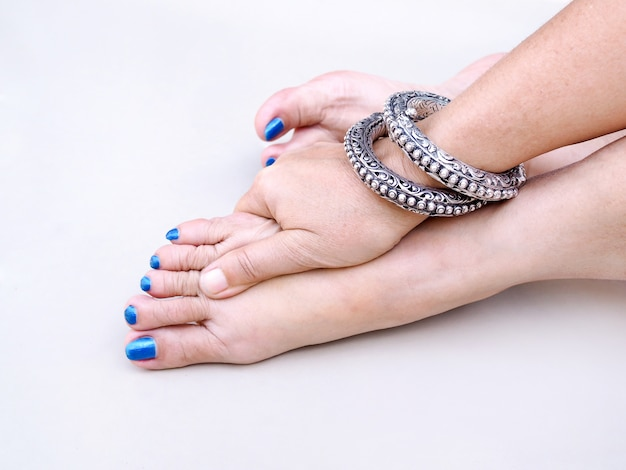 Взрослая азиатская женщина с синими ногтями на ногах и пользой на запястье, использует массаж рук на ногах, чтобы расслабиться.