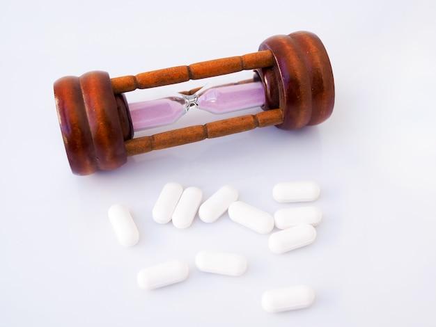 砂時計と鎮痛剤、薬の錠剤、時間と医療の概念。白い表面に分離されました。
