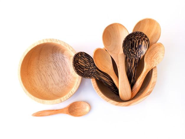 カップ、ボウル、白い表面に分離されたタイから手作りの木製スプーン入りスナック。
