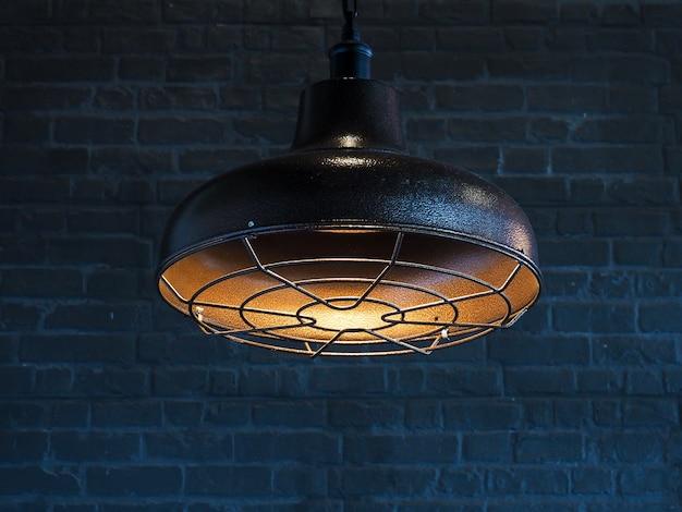 黒のレンガの壁と天井のインテリアデザインに掛かっているランプ