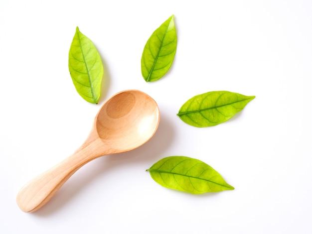 木のスプーンと緑の葉、自然な木製の道具エコフレンドリーで健康のために安全