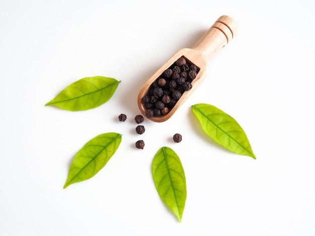 緑の葉と木のスプーンで黒コショウで穀物乾燥食品の全粒粉の上