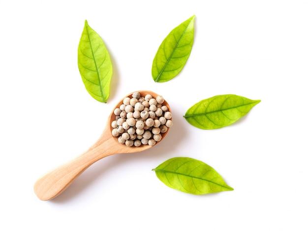 緑の葉と木のスプーンで白胡椒で穀物乾燥食品の全粒粉の上