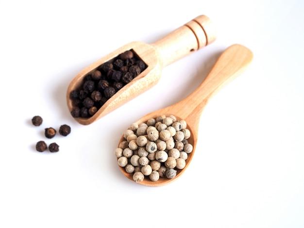 木のスプーンで黒コショウと白コショウで穀物乾燥食品の全粒粉の上