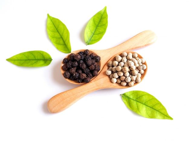 緑の葉と木のスプーンで黒コショウと白コショウの穀物乾燥食品全粒の上
