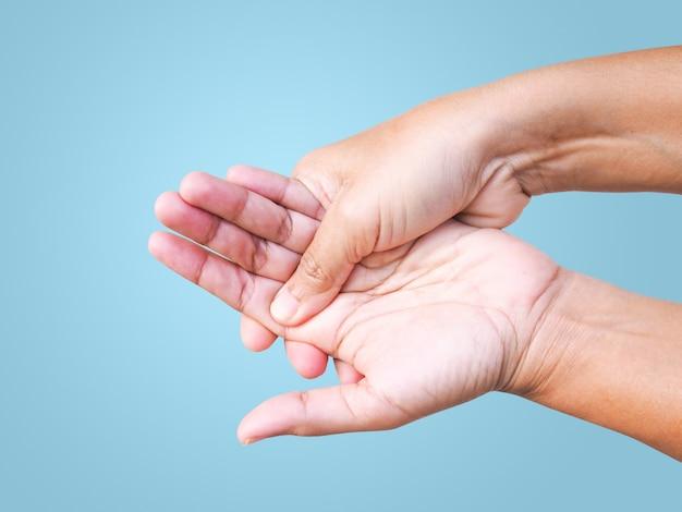 痛み、指の手の痛み、関節の痛みで苦しんでいるクローズアップの手。青色の背景に分離されました。