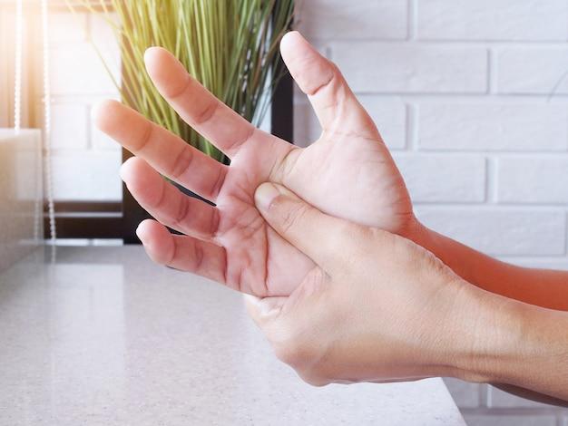 Конец-вверх руки женщин с массажем рук и ладони от боли и онемения.