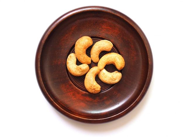 分離された木製のプレートにカシューナッツの上の、ダイエットの概念にきれいな食品を食べる。