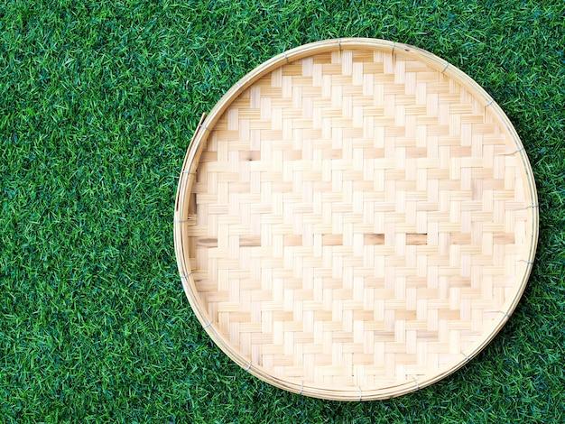 テキストのコピースペースまたはデザインのフレームと緑の草の背景に分離されたタイ料理のサークル竹織りトレイコンテナーの平面図です。