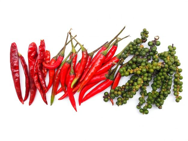 Вид сверху трав и специй с верхней рамкой из красного острого перца чили и сушеного чили и свежего зеленого перца