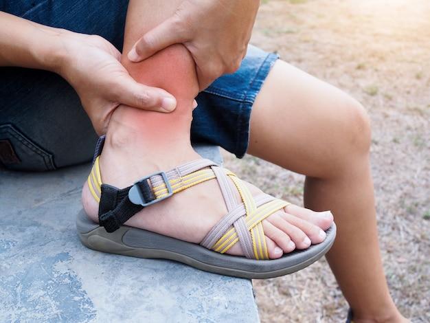 Молодая азиатская женщина страдая от ноги, травм ноги и воспаления мышц боли лодыжки.