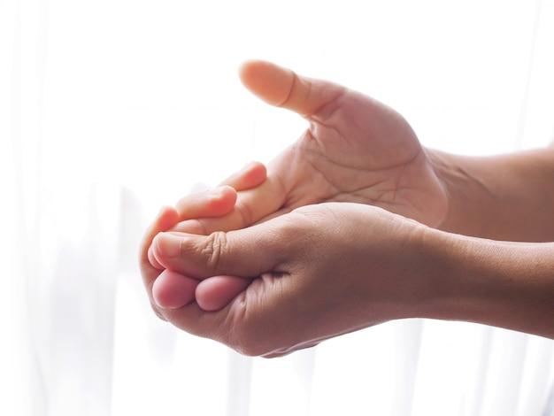 指の痛み、手の痛み、しびれを伴うアジアの女性。