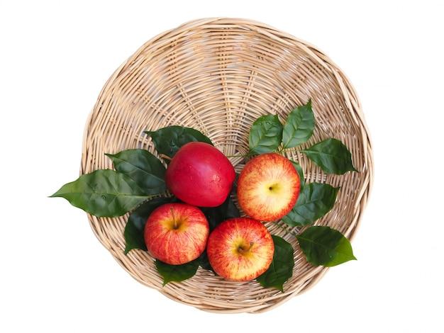 竹かごとクリッピングパスとホワイトスペースに分離された緑の葉の赤いフルーツリンゴのトップビュー