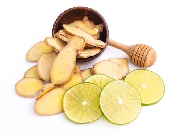 ハーブジンジャーとライムレモンの柑橘類とホワイトスペースに分離された蜂蜜とお茶の成分を飲みます。