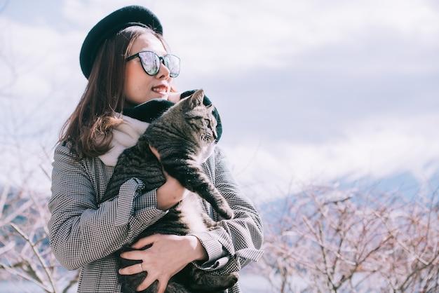 Азиатская женщина, держащая кошку на открытом воздухе в японии зимой