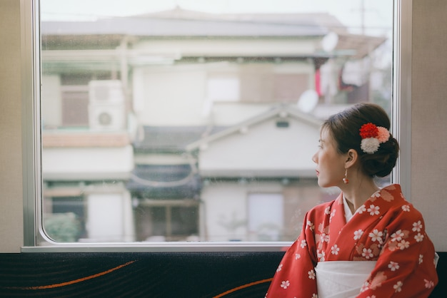 窓の近くに座って日本の古典的な電車で旅行着物を着ているアジアの女性