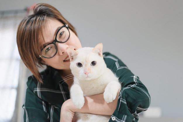 Азиатские женщины отдыхают в спальне с белым котом дома