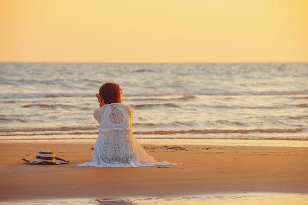 Молодая женщина стоит на пляже во время заката, летние каникулы.