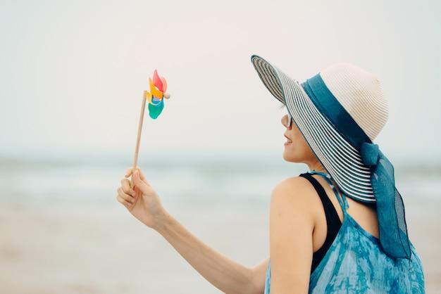 Женщина, наслаждаясь пляжного отдыха радостным летом на тропической голубой водой.