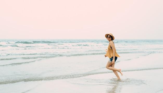 Женщина, наслаждаясь пляжным отдыхом, радостным летом у тропической голубой воды