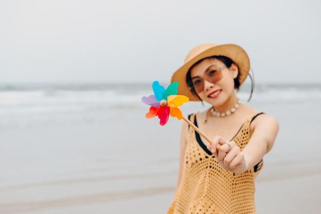 Женщина, наслаждаясь расслабляющий пляж радостным летом на тропической голубой водой. модель на путешествия носить шляпу пляжа.