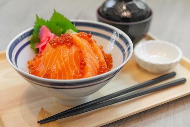 Японская еда лосось сашими, яйцо лосося (икура), тертый редис и ломтик имбиря с японским рисом донбури, лосось дон.