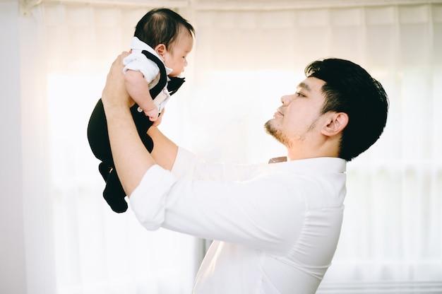 アジアの父が自宅で空気中の赤ん坊の息子を保持しています。