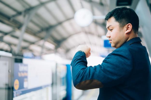 Азиатский бизнесмен смотрит на часы, ждет платформа поезда