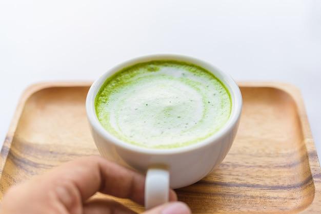木製のテーブル上のガラスのマッチョ緑茶ラテ飲料。