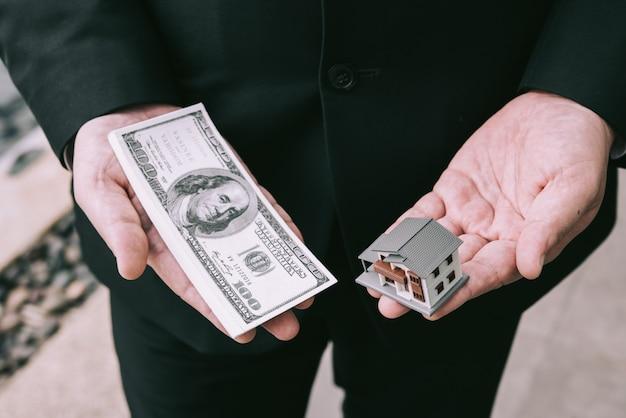 ミニチュアの家のおもちゃと男の手の中のお金。住宅ローンの概念。家とお金