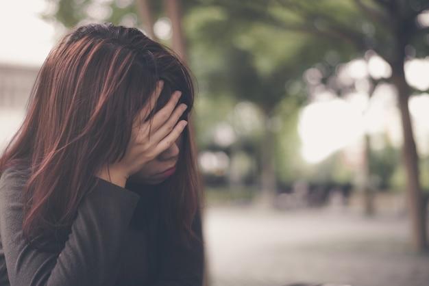 Азиатская женщина сидит в одиночестве и депрессии, портрет усталой молодой женщины. депрессия