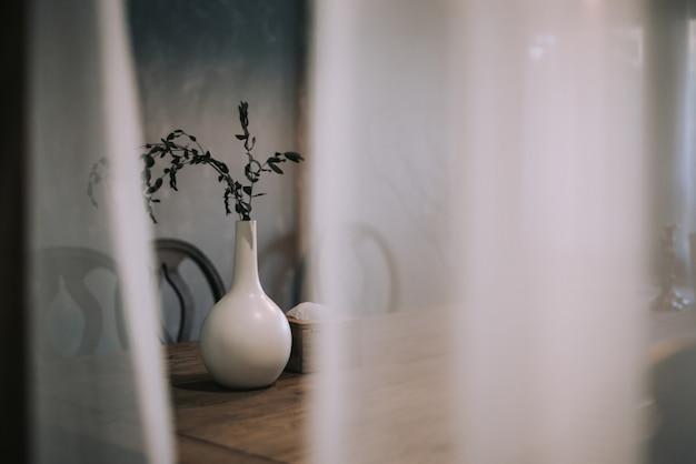 ドライブランチと白い花瓶は木製のテーブルの上に立ちます。部屋のミニマルデザイン。