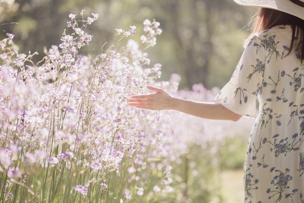 花の分野で彼女の麦わら帽子を持つ少女、花畑で楽しんで幸せな女