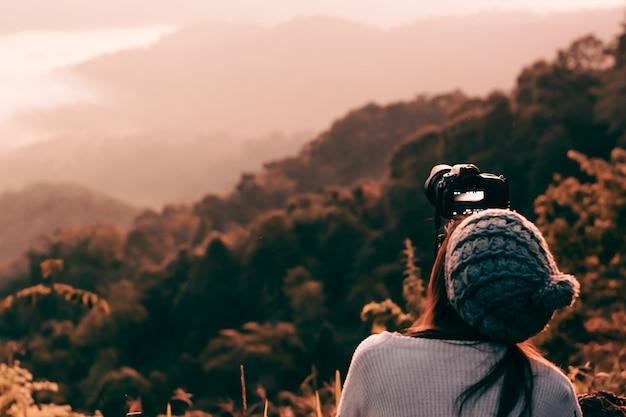 山頂で日の出時の風景の写真を撮る若い女性写真家。