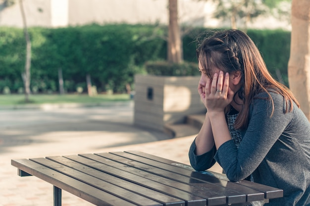 Грустная, расстроенная и взволнованная женщина, сидящая одна на улице