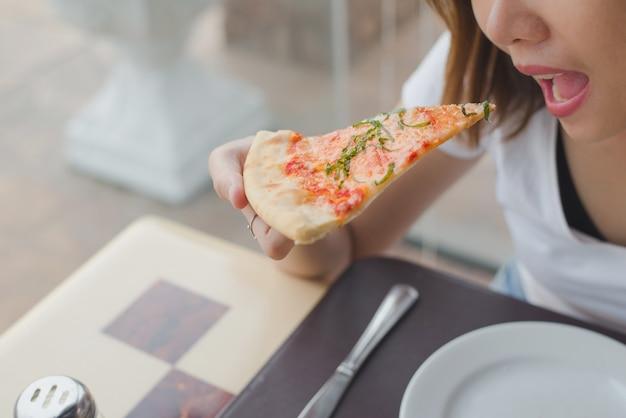 レストランでおいしいマルガリータピザを食べる女性。