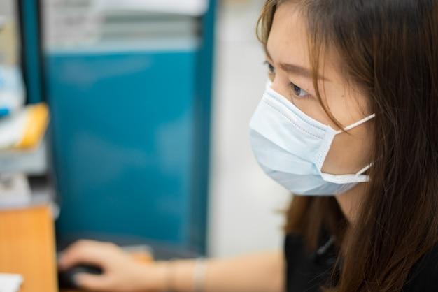 アジアの女性の病気や身に着けているフェイスマスクはオフィスで保護します