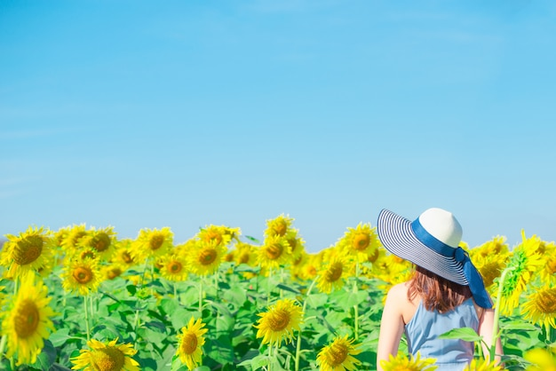 ひまわり畑で楽しんでいる花の分野で帽子を持つアジアの女性