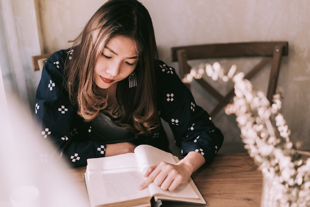 アジアの女性は木製のテーブルのそばに座って本を読んでいます。