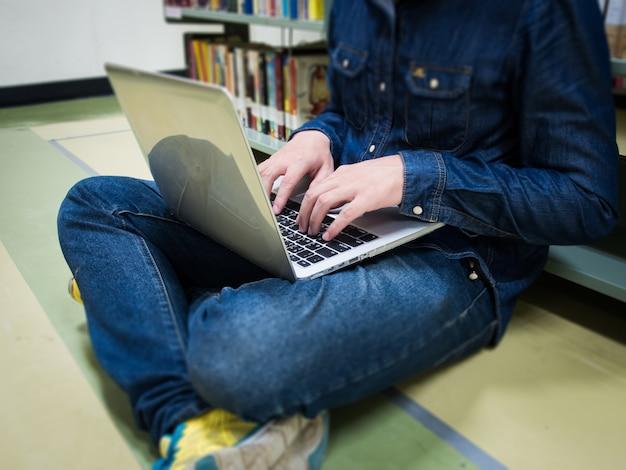 図書館でコンピュータを使う学生