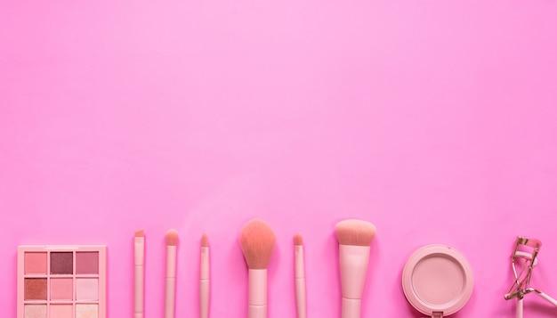 ピンクの背景のプロのメイクのトップビュー構成。