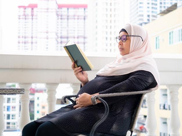 妊娠中の女性は笑顔で彼女の手に本を読んでいる。
