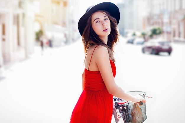 屋外自転車で笑顔のかわいい女の子。クローズアップの肖像画。